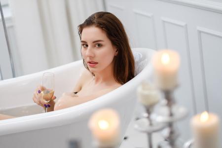 Frau liegt in einer Badewanne mit einem Glas Champagner