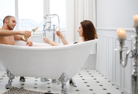 Couple laying in a bath with glass of champagne Banco de Imagens
