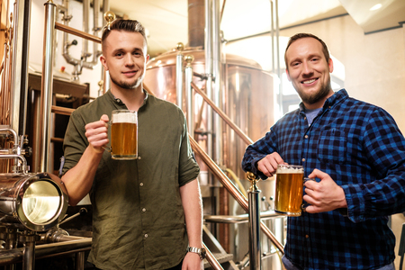 Two men tasting fresh beer in a brewery