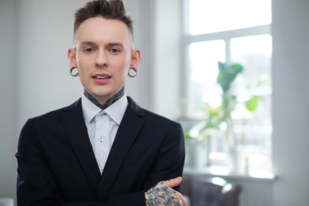 Portrait of alternative model with earplugs and tattoo
