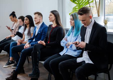 Groupe de jeunes en attente d'un casting ou d'un entretien d'embauche Banque d'images