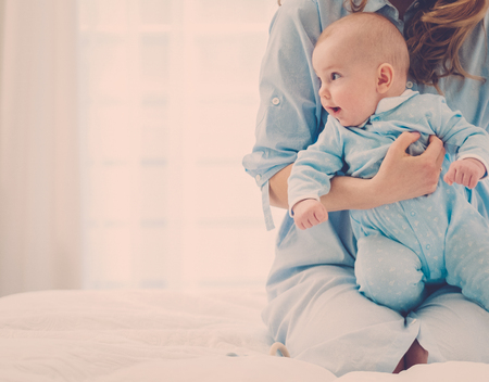 Happy middle aged mother with her child in a bed Stock Photo - 122592779
