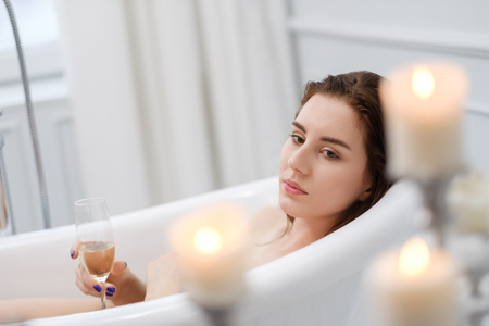 Woman laying in a bath with glass of champagne