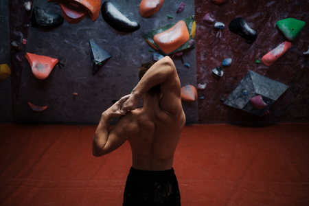 Athletic man stretching before climbing in a bouldering gym Stock Photo