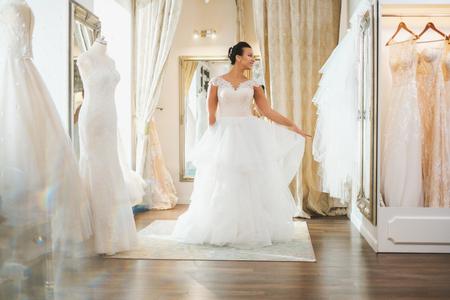Beautifu bride choosing wedding dress in a wedding salon 写真素材 - 124309355