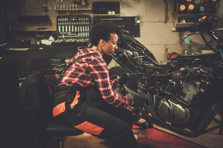 African american woman mechanic repairing a motorcycle in a workshop Stock Photo