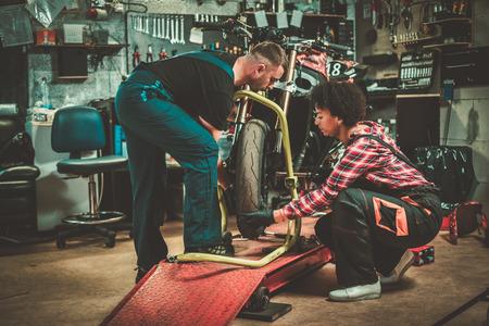 Mechanic and his helper repairing a motorcycle in a workshop