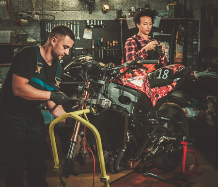 Mechanic and his helper repairing a motorcycle in a workshop