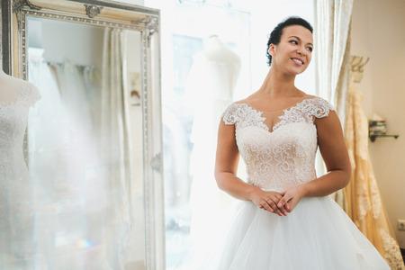 Beautifu bride choosing wedding dress in a wedding salon