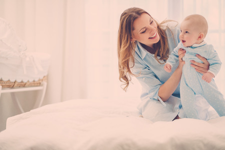Happy middle aged mother with her child in a bed Stock Photo - 124309611