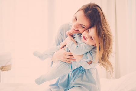 Beautiful middle aged mother with her child in a bed Stock Photo - 124309618