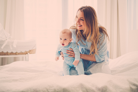 Beautiful middle aged mother with her child in a bed
