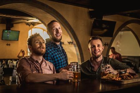Freunde trinken Bier vom Fass und fernsehen in einer Kneipe Standard-Bild