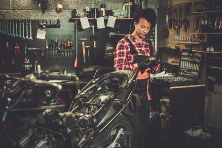 Afroamerikanische Mechanikerin, die ein Motorrad in einer Werkstatt repariert