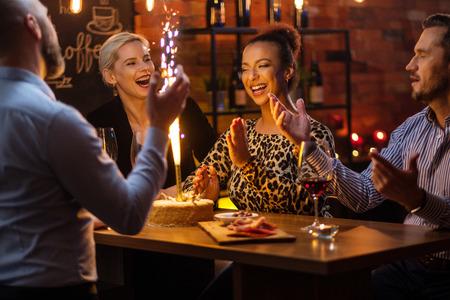 Groep vrienden die verjaardag vieren in een café achter de toog