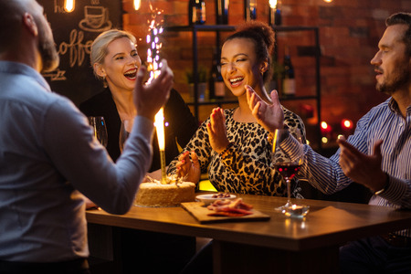 Grupo de amigos celebrando un cumpleaños en un café detrás de barra de bar