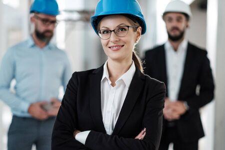 Ingenieros en cascos posando en edificio nuevo