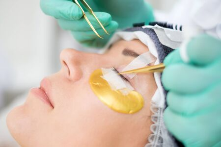 Procedure of eyelash extension in salon by cosmetician