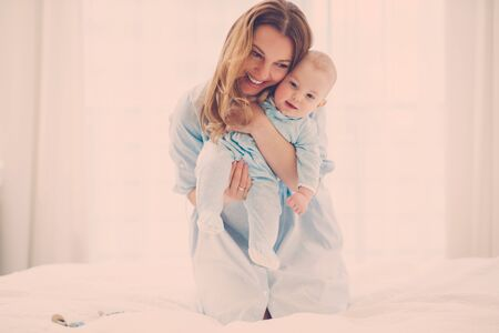 Happy middle aged mother with her child in a bed Stock Photo - 125680789