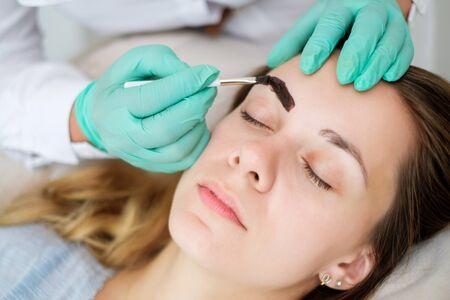 Esthéticienne effectuant la correction des sourcils au henné