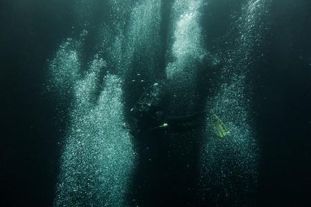 Scuba divers swimming under water Imagens