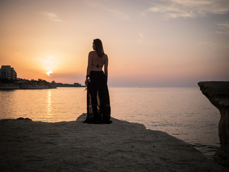 Woman looking on a resort town at dusk Stock Photo