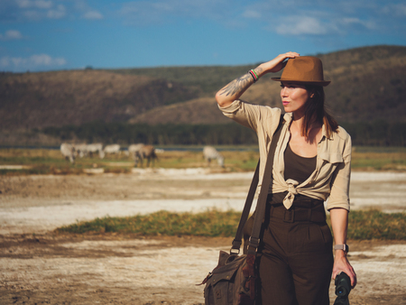 Beautiful woman with binoculars at savanna in Kenya