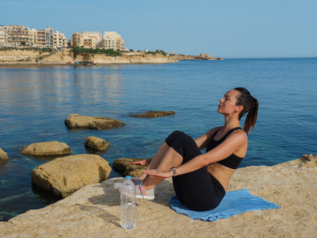 Woman doing fitness exercise near water on Gozo island