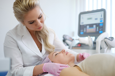Woman getting treatment with aesthetic dermatology device
