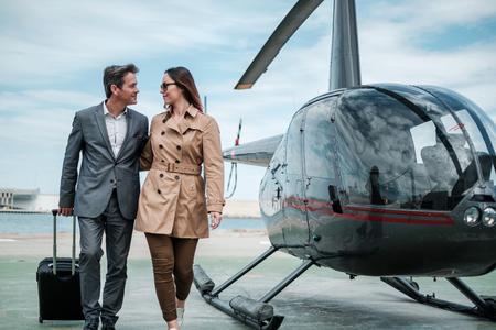 Jong zakenpaar dichtbij privéhelikopter Stockfoto