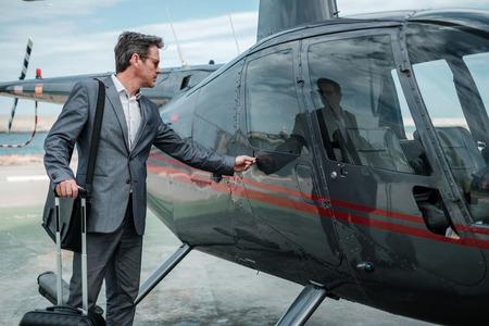 Homme d'affaires parlant au téléphone portable près d'un hélicoptère privé