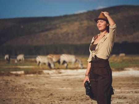 Beautiful woman with binoculars at savanna in Kenya 写真素材