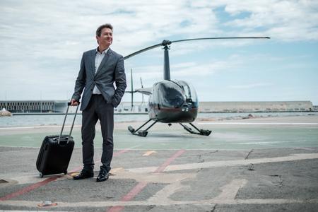 Biznesmen stojący w pobliżu prywatnego helikoptera
