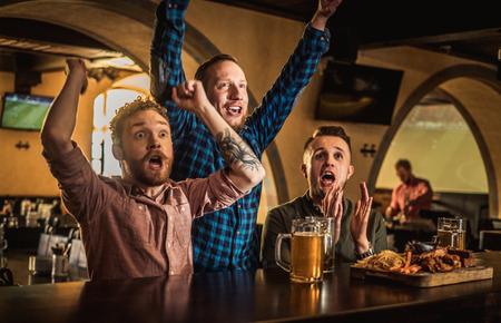 Amigos bebiendo cerveza de barril y viendo la televisión en un pub