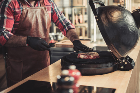 Chef grilling steak in a restaurant Stock Photo