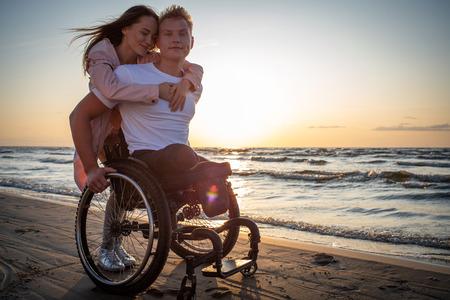 Hombre discapacitado en silla de ruedas y su novia en una playa al atardecer