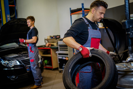 Car mechanic mounts tire on wheel in a workshop