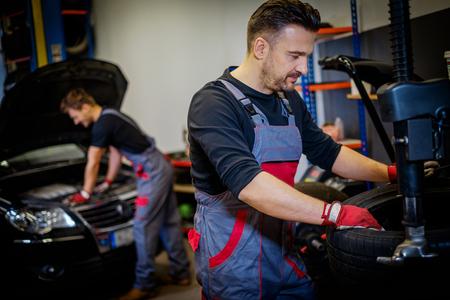 Car mechanic mounts tire on wheel in a workshop