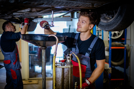 Car mechanic changes oil in a workshop
