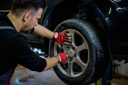 Car mechanic replacing wheel in a workshop