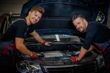 Car mechanics checking under hood in a workshop Zdjęcie Seryjne