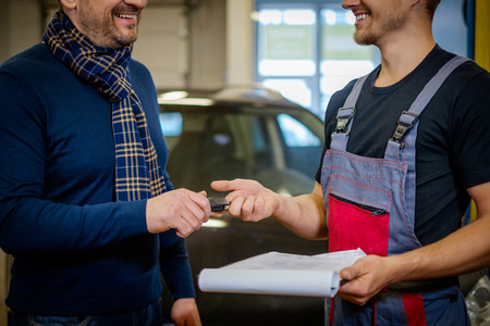 Mechanic givies client keys to his repaired car in a workshop