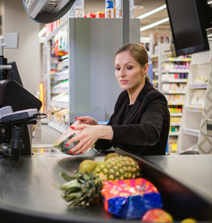 Woman cashier working in a grocery store