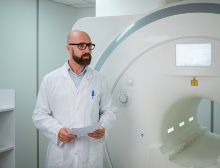 Doctor with a patient medical card near MRI scanner in a hospital Zdjęcie Seryjne