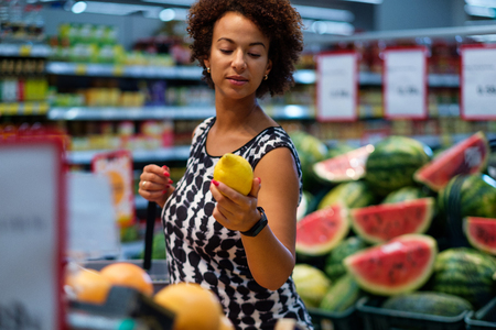 Pretty black woman choosing fruits in a grocery store