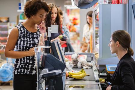 Femme noire achetant des marchandises dans une épicerie