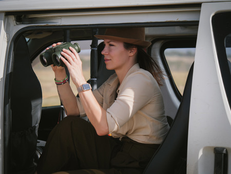 Woman on a safari trip in Masai Mara park, Kenya