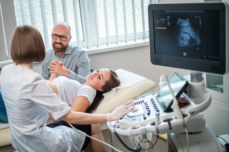 Zwangere vrouw en haar man bij utltrasonografisch onderzoek in het ziekenhuis