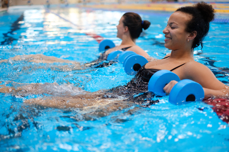 Multiracial couple attending water aerobics class in a swimming pool 스톡 콘텐츠