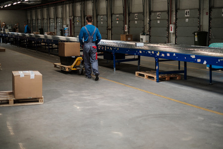 Warehouse worker with a pallet rack Фото со стока